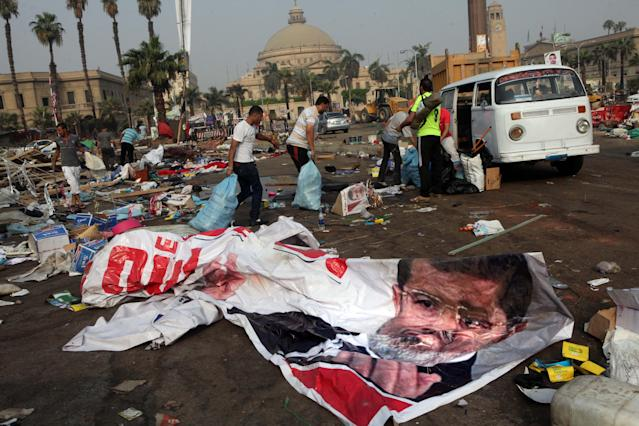 Egyptians remove valuables they collected from debris in a protest camp next to a banner depicting Egypt's ousted President Mohammed Morsi in Nahda Square, Giza, Cairo, Egypt, Thursday, Aug. 15, 2013. Egypt faced a new phase of uncertainty on Thursday after the bloodiest day since its Arab Spring began, with over 300 people reported killed and thousands injured as police smashed two protest camps of supporters of the deposed Islamist president. Wednesday's raids touched off day-long street violence that prompted the military-backed interim leaders to impose a state of emergency and curfew, and drew widespread condemnation from the Muslim world and the West, including the United States. (AP Photo/Amr Nabil)