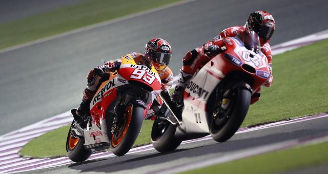 Honda MotoGP rider Marc Marquez (L) of Spain rides his bike during a free practice session at the MotoGP World Championship at the Losail International circuit in Doha March 20, 2014. REUTERS/Mohammed Dabbous (QATAR - Tags: SPORT MOTORSPORT)