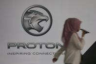 A woman walks past a logo of Proton at its headquarters in Subang Jaya
