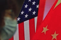 A woman wearing a face mask to help curb the spread of the coronavirus sits near a screen showing China and U.S. flags as she listens to a speech by Chinese Foreign Minister Wang Yi at the Lanting Forum on bringing China-U.S. relations back to the right track, at the Ministry of Foreign Affairs office in Beijing on Monday, Feb. 22, 2021. Foreign Minister Wang Yi called on the U.S. Monday to lift restrictions on trade and people-to-people contacts while ceasing what Beijing considers unwarranted interference in the areas of Taiwan, Hong Kong, Xinjiang and Tibet. (AP Photo/Andy Wong)