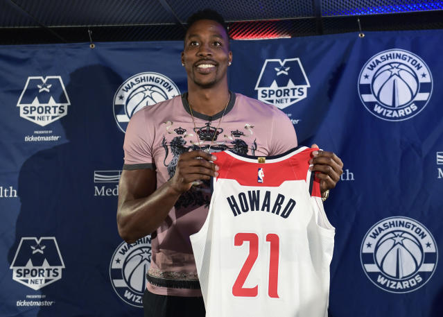 "<a class=""link rapid-noclick-resp"" href=""/nba/players/3818/"" data-ylk=""slk:Dwight Howard"">Dwight Howard</a> poses with his Wizards jersey at Monday's news conference. (AP)"