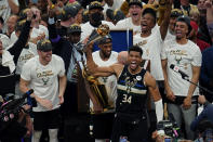 Milwaukee Bucks forward Giannis Antetokounmpo (34) reads with the championship trophy after defeating the Phoenix Suns in Game 6 of basketball's NBA Finals in Milwaukee, Tuesday, July 20, 2021. The Bucks won 105-98. (AP Photo/Paul Sancya)