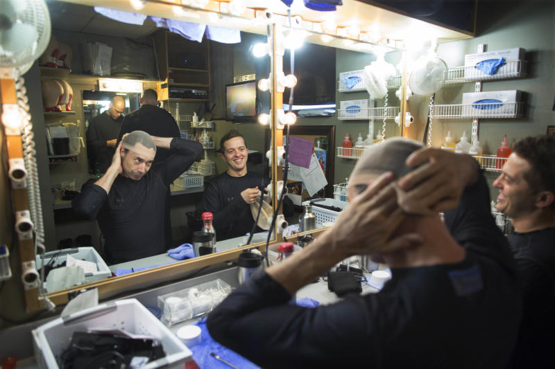 In this July 10, 2013, photograph, current members of the Blue Man Group, from left reflected in the mirror, Scott Bishop, Eric Gebow and Collin Batten prepare to get into character backstage at the Briar Street Theatre. The Blue Man Group recently held open auditions in Chicago hoping to add to their recently expanded shows throughout the world. (AP Photo/Scott Eisen)