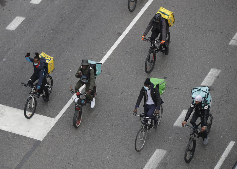FILE - In this Nov. 5, 2020 file photo, food delivery riders stage a protest against the government restriction measures to curb the spread of coronavirus in Milan, Italy. Italy is cracking down on bike delivery service companies, with one Milan prosecutor saying the riders, most of them immigrants, are practically treated like slaves. Milan prosecutors on Wednesday told a news conference that four delivery companies in Italy have been given 90 days to improve their treatment of riders. (AP Photo/Luca Bruno)