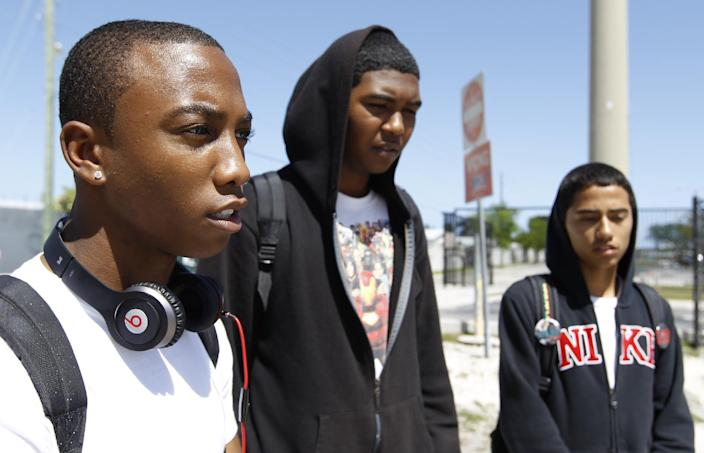 John Emmanuel, left, talks about Trayvon Martin, a 17-year-old who was shot and killed by a neighborhood watchman a couple of weeks ago in Sanford, Fla., as Mackenzie Baksh, center, and Brian Paz, right, look on Thursday, March 22, 2012, in Miami Gardens, Fla. (AP Photo/Luis M. Alvarez)