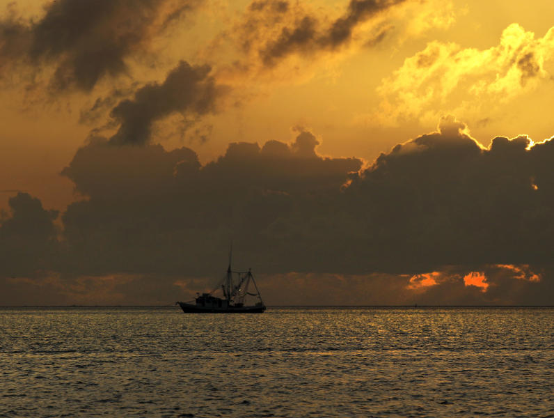 FILE - In this May 20, 2010 file photo, a shrimp boat carrying oil collection booms anchors for the night in Gulf of Mexico off the Mississippi River delta south of Venice, La. It will be months before state officials know whether losses from floods and spillway openings qualify Louisiana as a fisheries disaster. Department of Wildlife and Fisheries officials say floods began around November 2018, and a full 12 months' data is needed to compare to averages for the previous 5 years. The governors of Louisiana, Mississippi and Alabama asked months ago for US Commerce Secretary Wilbur Ross to declare a fisheries disaster, making federal grants available to affected people. (AP Photo/Charlie Riedel, File)