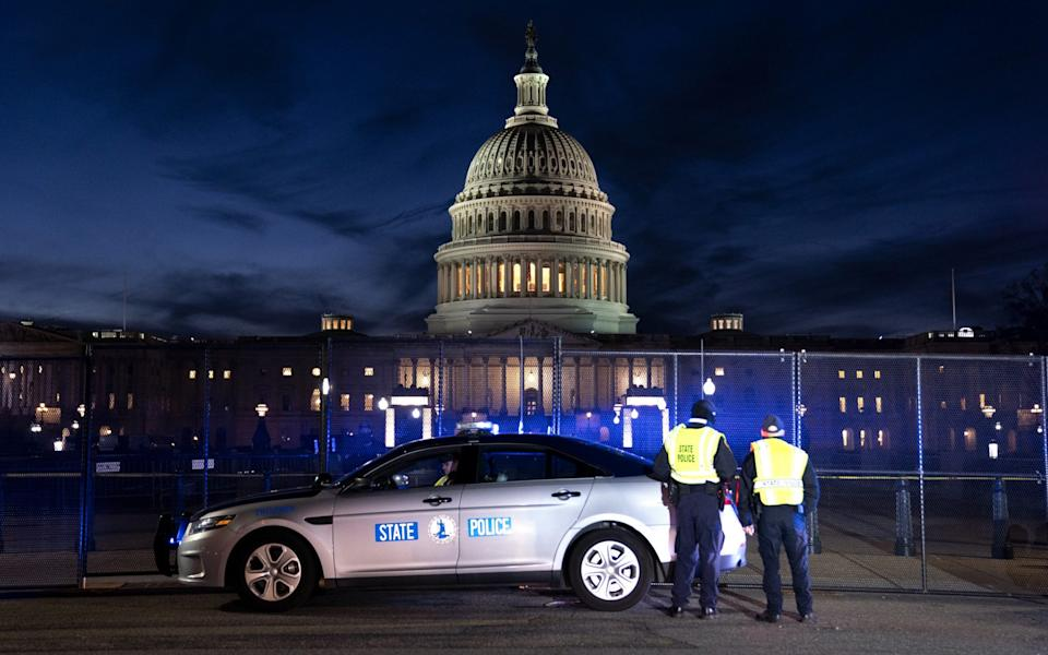 Police keep watch outside the Capitol on Thursday evening - BLOOMBERG