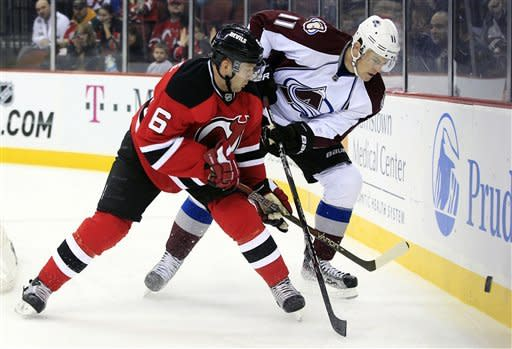 Colorado Avalanche's Jamie McGinn (11) tries to get to the puck ahead of New Jersey Devils' Andy Greene (6) during the first period of an NHL hockey game in Newark, N.J., Thursday, March 15, 2012. (AP Photo/Mel Evans)