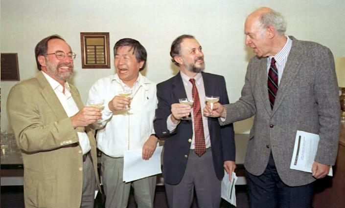 Four men toast each other
