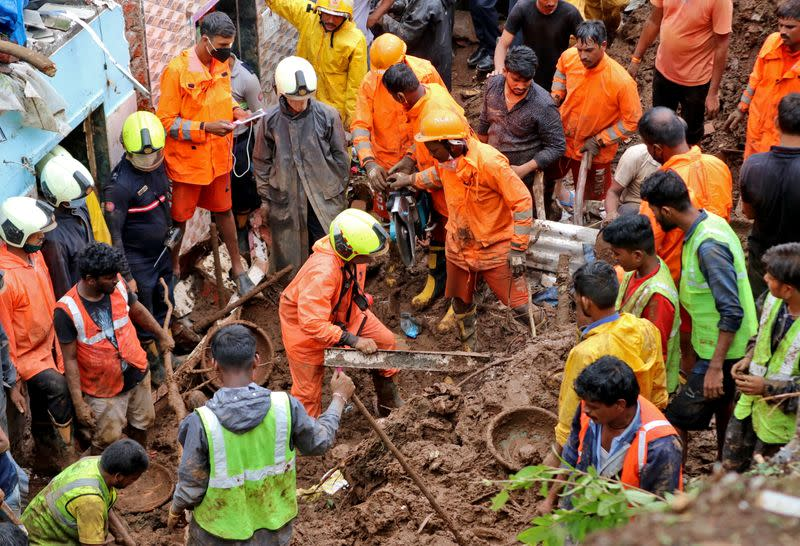 Rescue workers remove debris as they search for survivors after a residential house collapsed due to landslide caused by heavy rainfall in Mumbai