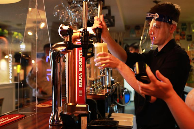 A member of staff wearing a PPE visor pours a pint inside the Black Horse Inn in Haxby, York, on Super Saturday as pubs and other stores reopen after lockdown measures are relaxed in England
