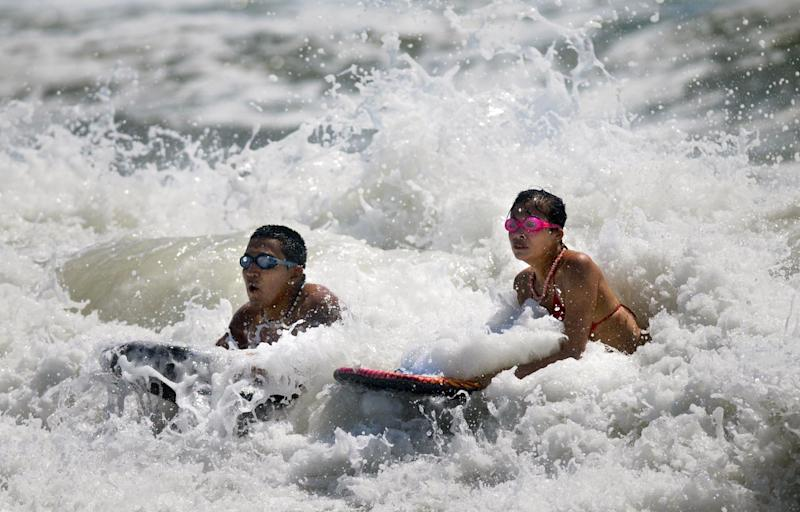 Joel Izaguirre, left, and Dorian Hernandez of Dunn ride some heavy surf at Carolina Beach, N.C. Saturday, May 26, 2012. Strong rip currents created dangerous swimming conditions and prompted Carolina Beach Ocean Rescue to close the beach to swimming and not allow people in past their knees. (AP Photo/The Star-News,Matt Born )