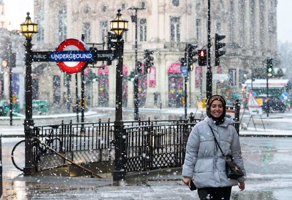 A woman walks through falling snow in Piccadilly Circus, in central London. Picture date: Sunday January 24, 2021. (Photo by Dominic Lipinski/PA Images via Getty Images)
