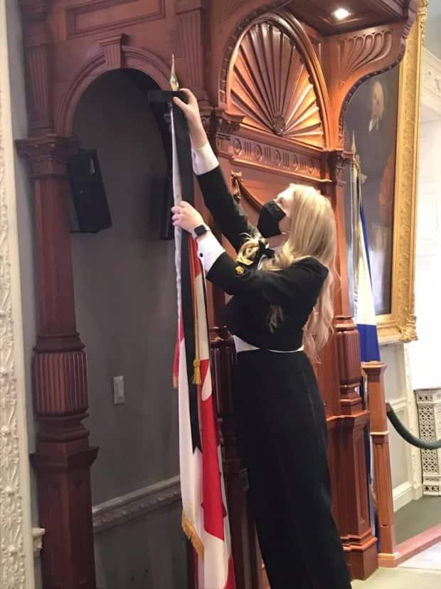 Page Charlotte Moase places a black ribbon on the flag pole that sits to the right of the Speaker's chair in the legislative chamber at Province House.  (Kelly Regan/Facebook - image credit)