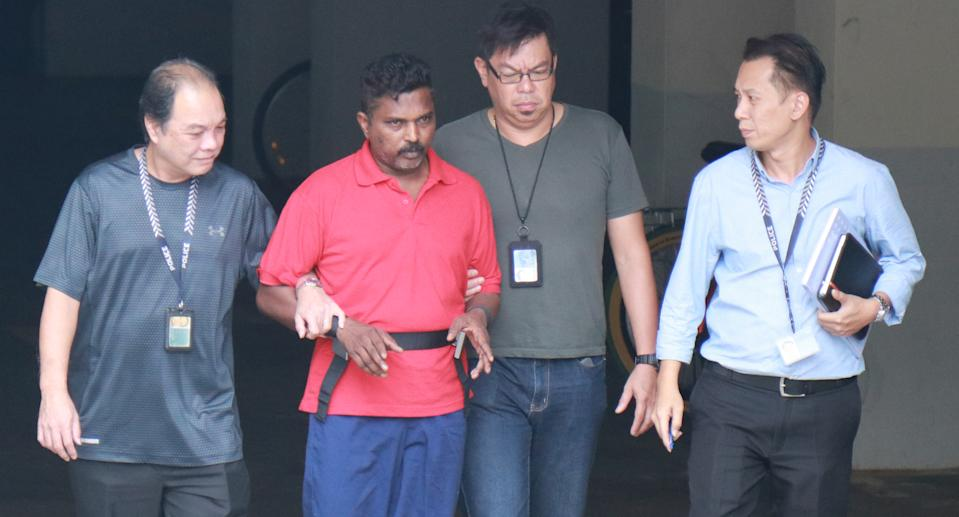 On 1 November 2017, Krishnan Raju (in red) was escorted by officers to the Loyang Gardens condominium on Jalan Loyang Besar where he allegedly killed 44-year-old Raithena Vaithena Samy. Photo: Yahoo News Singapore