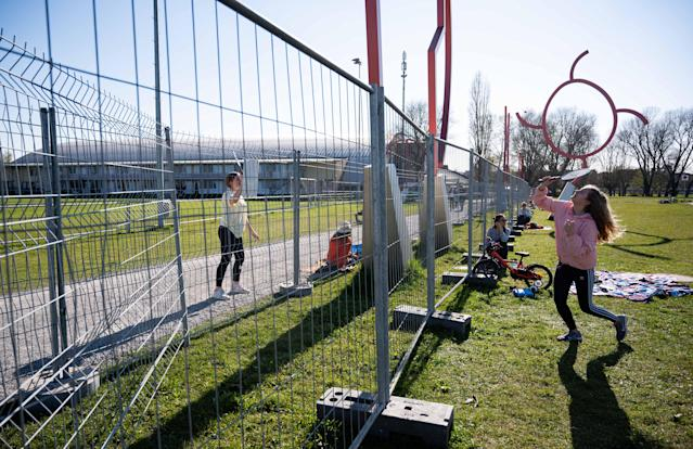 KONSTANZ, GERMANY - APRIL 06: Two girls play badminton from two fences in order to stop physical contact along the Germany-Switzerland border during the coronavirus crisis on April 6, 2020 in Konstanz, Germany. Cross-border travel has been temporarily banned in an effort to stem the spread of the virus. Authorities recently added the double fence at Konstanz in order to prevent lovers, of which one lives in Germany and the other in Switzerland, from meeting there and hugging. Many people who live on the Germany side of the border work in Switzerland. (Photo by Daniel Kopatsch/Getty Images)