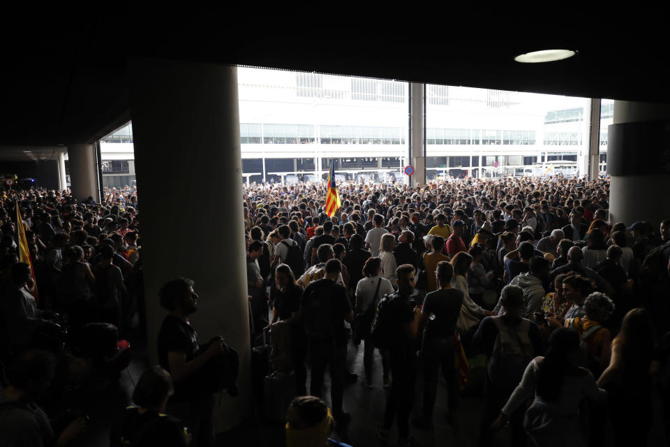 An Estelada pro-independence flag is waved among protestors at El Prat airport in Barcelona, Spain, Monday, Oct. 14, 2019. Spain's Supreme Court on Monday convicted 12 former Catalan politicians and activists for their roles in a secession bid in 2017, a ruling that immediately inflamed independence supporters in the wealthy northeastern region. (AP Photo/Emilio Morenatti)