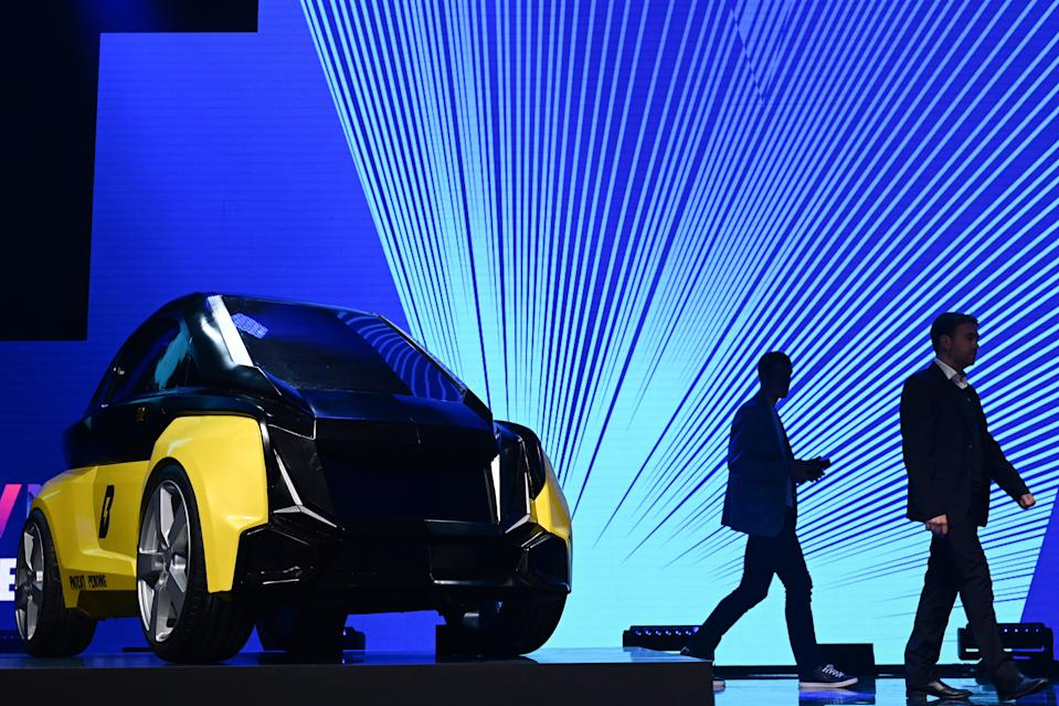 Two men walk past a prototype of a two seater electric car made by the Bolt Mobility company, which is displayed during the Vivatech startups and innovation fair, in Paris on May 16, 2019. (Photo by Philippe LOPEZ / AFP)        (Photo credit should read PHILIPPE LOPEZ/AFP via Getty Images)
