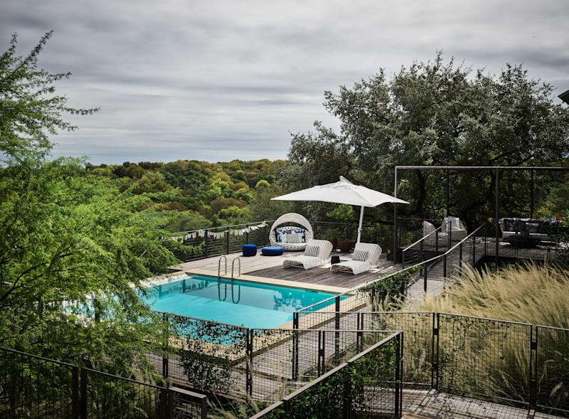 """""""I wanted the backyard to feel wild and free,"""" says McFayden, who commissioned Mark Word of Austin's Word + Carr to clean up the outdoor area with a series of decks, ramps, and walkways supported by piers and cable railing."""