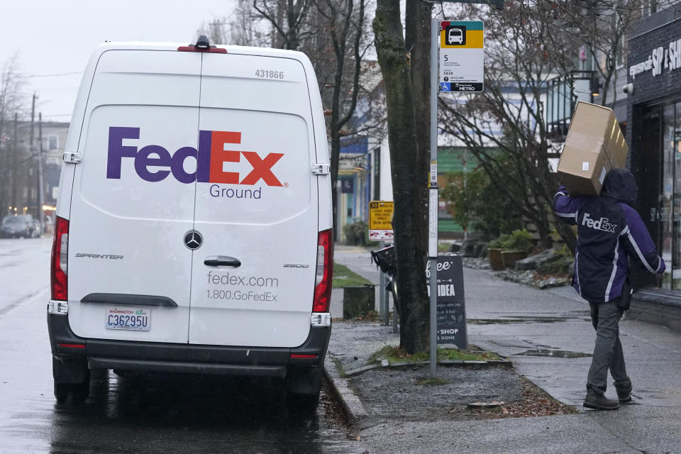 FILE - In this Tuesday, Dec. 8, 2020, file photo, a driver with FedEx carries a package away from a van, in Seattle. FedEx says its profit nearly tripled in its most recent quarter, despite winter weather that hobbled some of its facilities. Online shopping has surged during the pandemic as more people avoid going inside stores. That has made package delivery companies like FedEx in high demand. (AP Photo/Ted S. Warren, File)