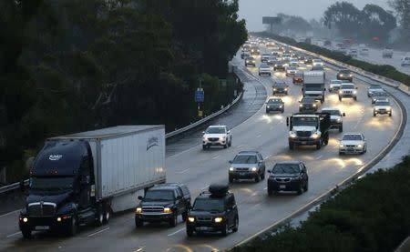 Traffic moves through the rain along interstate 5 in Encinitas, California December 3, 2014. Nearly two-thirds of Americans would support roadway user fees to help fix the country's crumbling transportation infrastructure, according to a survey to be published on April 28, 2016 that was seen by Reuters.   REUTERS/Mike Blake/File Photo