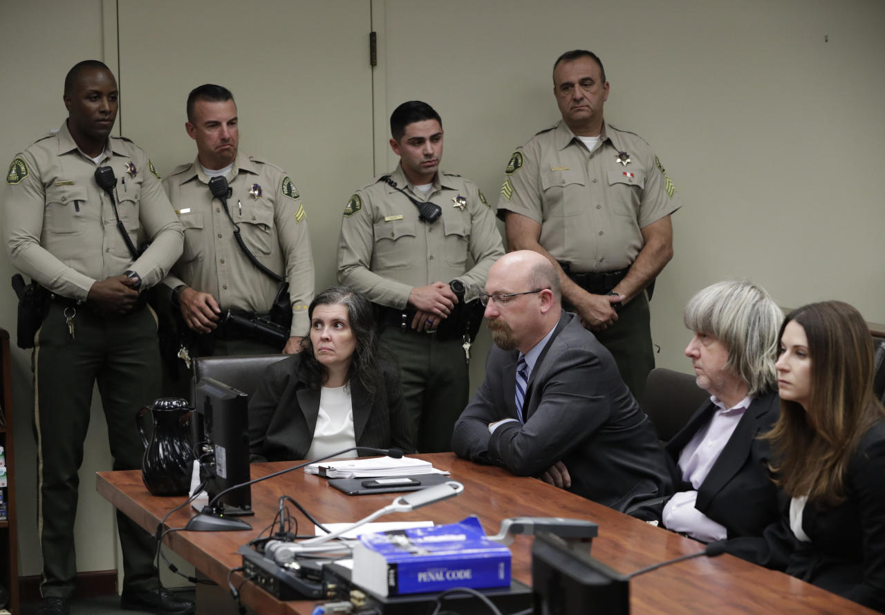 FILE--In this Jan. 18, 2018, file photo, defendants Louise Anna Turpin, left, with attorney Jeff Moore, and David Allen Turpin, right, with attorney Allison Lowe, appear in court for their arraignment in Riverside, Calif. More than $120,000 has been donated to help 13 siblings in California who authorities say were kept chained to beds for months by their parents, the Turpins, and starved so much that their growth was stunted. (Los Angeles Times/Gina Ferazzi via AP, Pool, file)