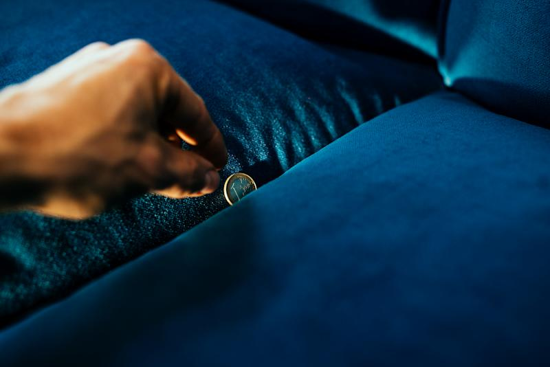 Hand and coin between sofa pillows.
