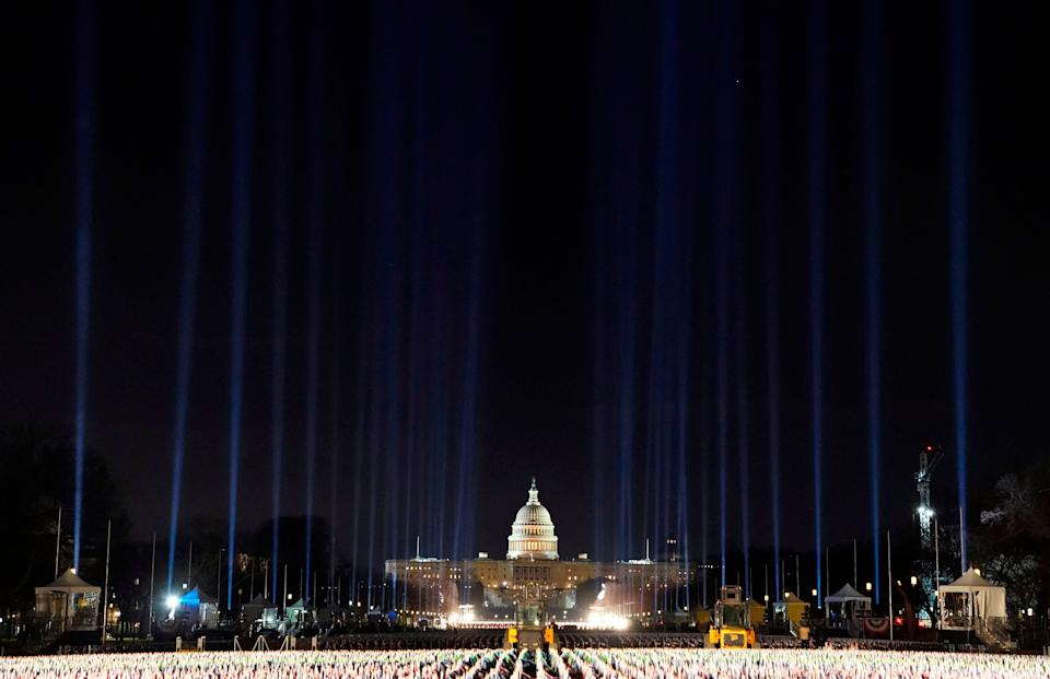 """Lights were beamed into the sky surrounding the """"Field of Flags"""" as inauguration week kicked off Monday. (Photo: TIMOTHY A. CLARY via Getty Images)"""