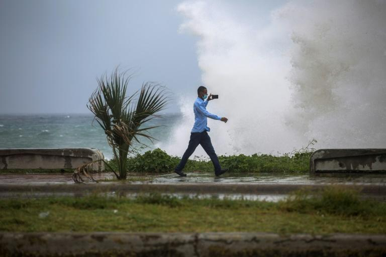 A man records a video of the strong waves caused by tropical storm Elsa at the Malecon in Santo Domingo, Dominican Republic on July 3, 2021