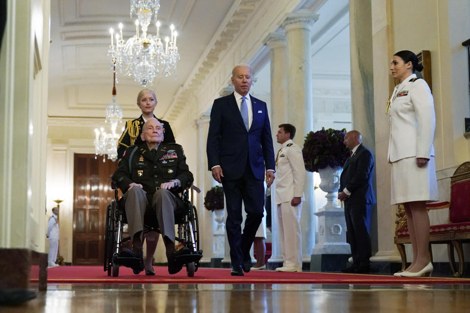 FILE - In this May 21, 2021, file photo President Joe Biden arrives with retired U.S. Army Col. Ralph Puckett, who will be presented the Medal of Honor, in the East Room of the White House in Washington. Thanks to growing availability of the coronavirus vaccine and a recent relaxation of federal guidance on masks and distancing, the Biden administration is embracing the look and feel of pre-pandemic days on Pennsylvania Avenue. (AP Photo/Alex Brandon, File)
