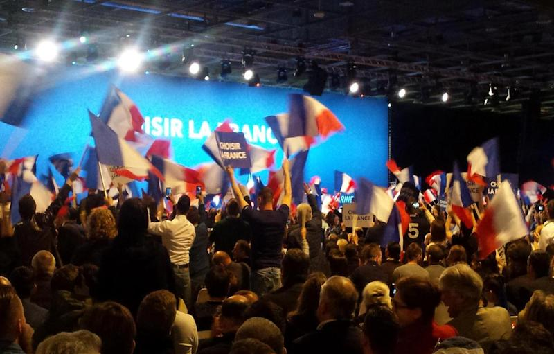 Marine Le Pen supporters cheer and wave their flags (The Independent)