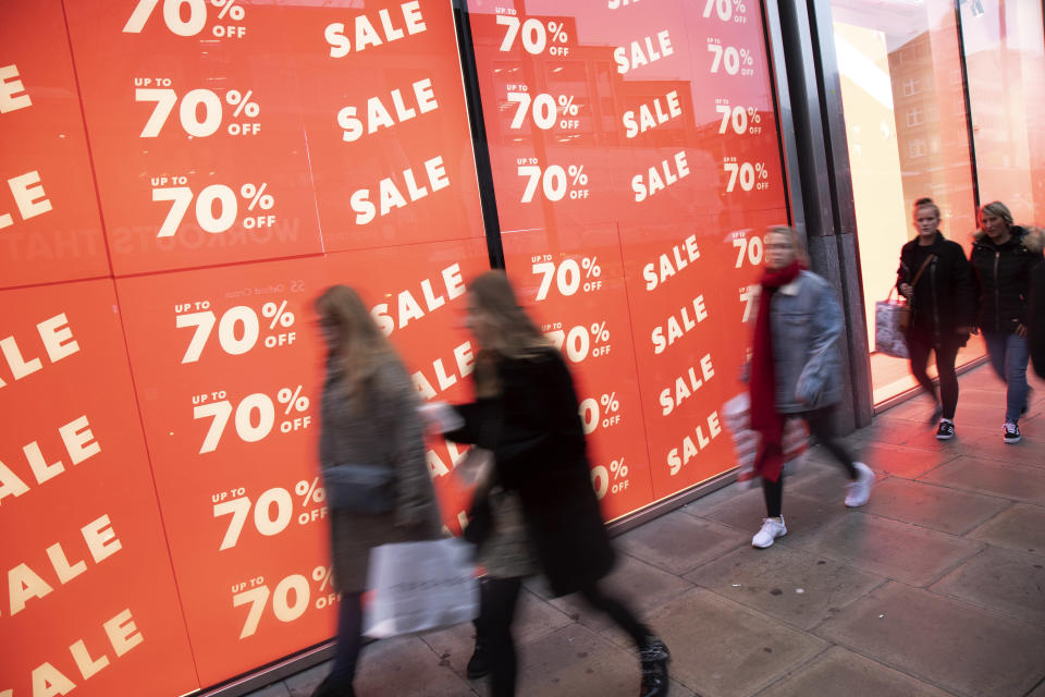 Tough conditions: People out shopping on Oxford Street walk past huge January sale signs in London. Photo: Mike Kemp/In Pictures via Getty Images.