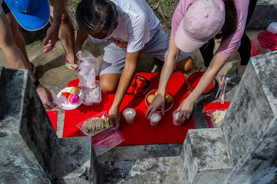 Family members clean and pray at the graves of their ancestors as a sign of respect and to honour their deceased relatives during the Qing Ming festival at the Kwong Tong Chinese Cemetery in Kuala Lumpur April 4, 2021. — Picture by Shafwan Zaidon