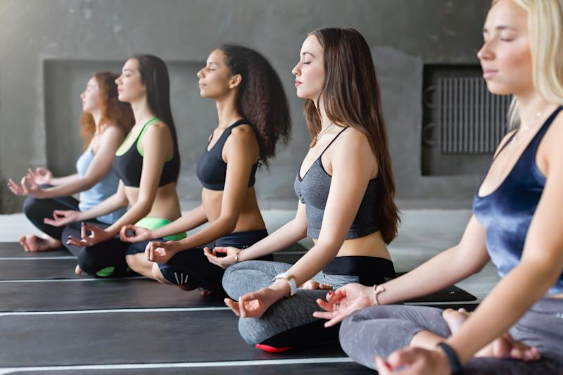Women in athletic apparel sitting on the floor in Sukhasana pose.