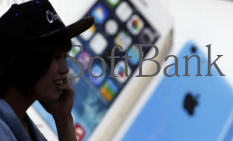 A pedestrian using a mobile phone walks past a shop window of Japan's mobile phone operator Softbank in Tokyo, September 20, 2013. REUTERS/Yuya Shino