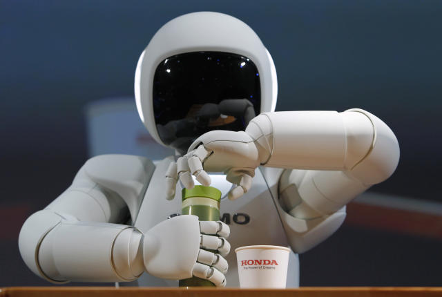 Honda Motor Co's Asimo humanoid robot opens the top of a bottle to pour the drink into a cup during a news conference at the 42nd Tokyo Motor Show in Tokyo November 30, 2011. REUTERS/Toru Hanai (JAPAN - Tags: BUSINESS SCIENCE TECHNOLOGY)