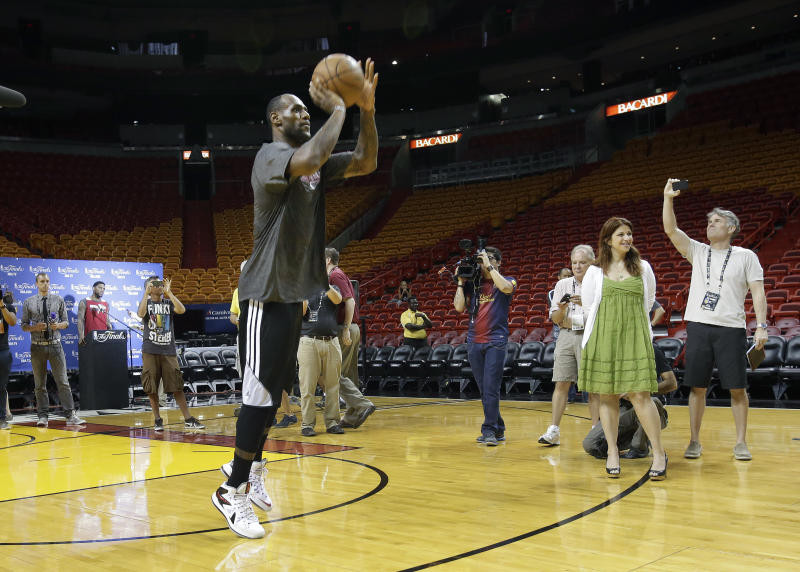 Miami Heat small forward LeBron James shoots across the court as he is watched by members of the media during basketball practice on Saturday, June 8, 2013, at the American Airlines Arena in Miami. The Heat and the San Antonio Spurs are to play Game 2 of the NBA Finals, Sunday. (AP Photo/Wilfredo Lee)