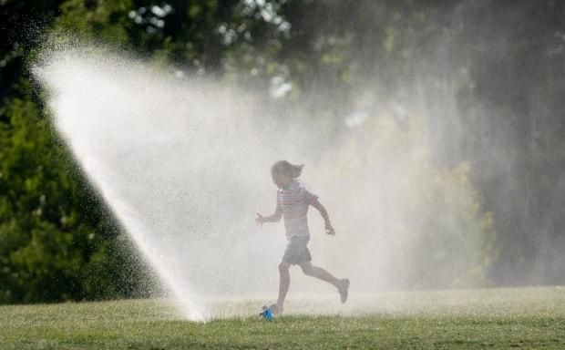 Josephine Young runs through a sprinkler near the Ottawa River last summer. People will be seeking out sprinklers and other ways to stay cool in the coming days as a heat warning has been issued for the Ottawa area. (Adrian Wyld/Canadian Press - image credit)