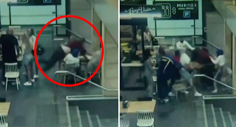 The alleged attacker leans over the table to reach the woman (left) before bystanders try to restrain him. Source: 7News