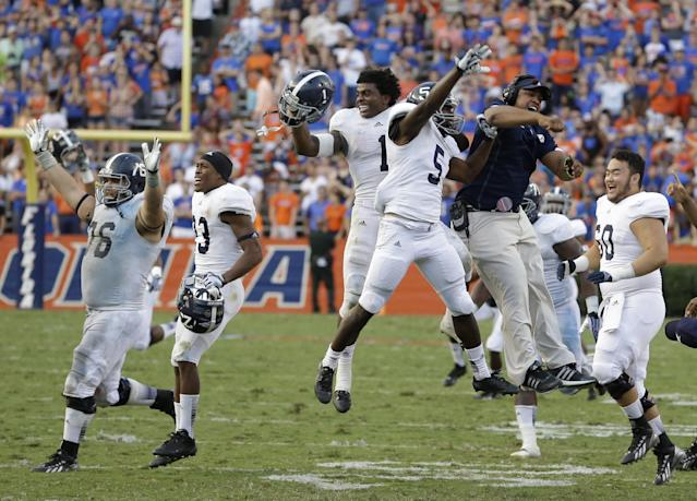 Georgia Southern players and coaches, including Jerick McKinnon (1) and Darius Jones (5) run out on the field celebrating after defeating Florida 26-20 in an NCAA college football game in Gainesville, Fla., Saturday, Nov. 23, 2013.(AP Photo/John Raoux)