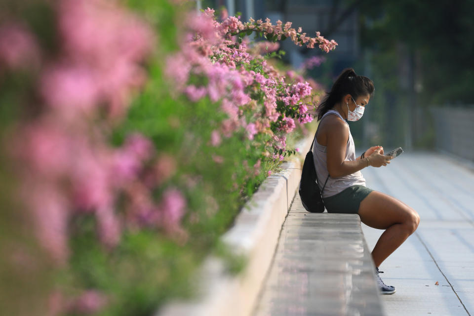 A woman wearing protective mask checks on her mobile phone on July 29, 2021 in Singapore.  (Photo by Suhaimi Abdullah/NurPhoto via Getty Images)