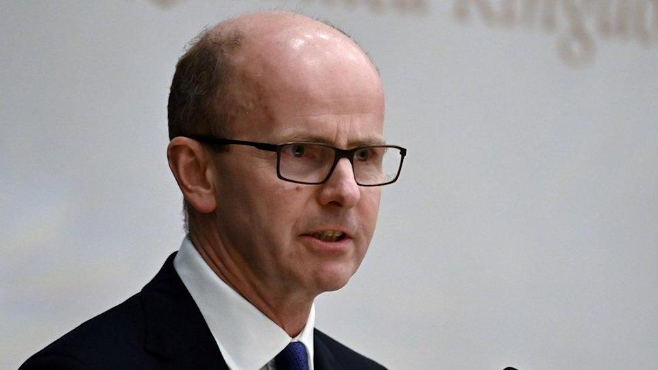 Jeremy Fleming stands against a white background, wearing glasses and a dark suit