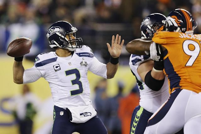 Seattle Seahawks' Russell Wilson (3) throws against the Denver Broncos during the first half of the NFL Super Bowl XLVIII football game Sunday, Feb. 2, 2014, in East Rutherford, N.J. (AP Photo/Julio Cortez)