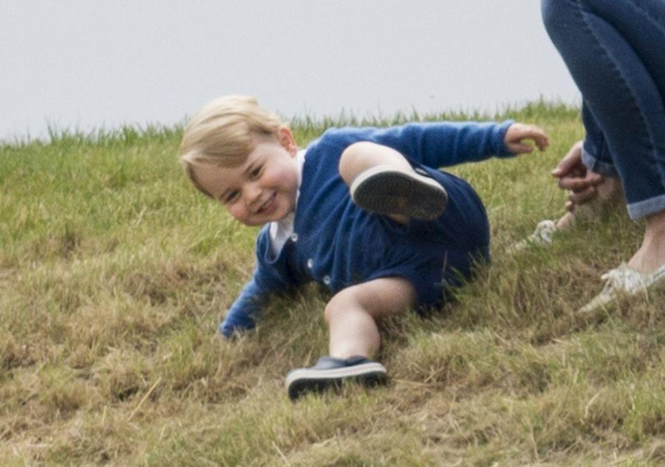 <p>Prince George, 11 months, slides down a hill while watching his dad Prince William and uncle Prince Harry play a charity match at the Beaufort Polo Club.</p>