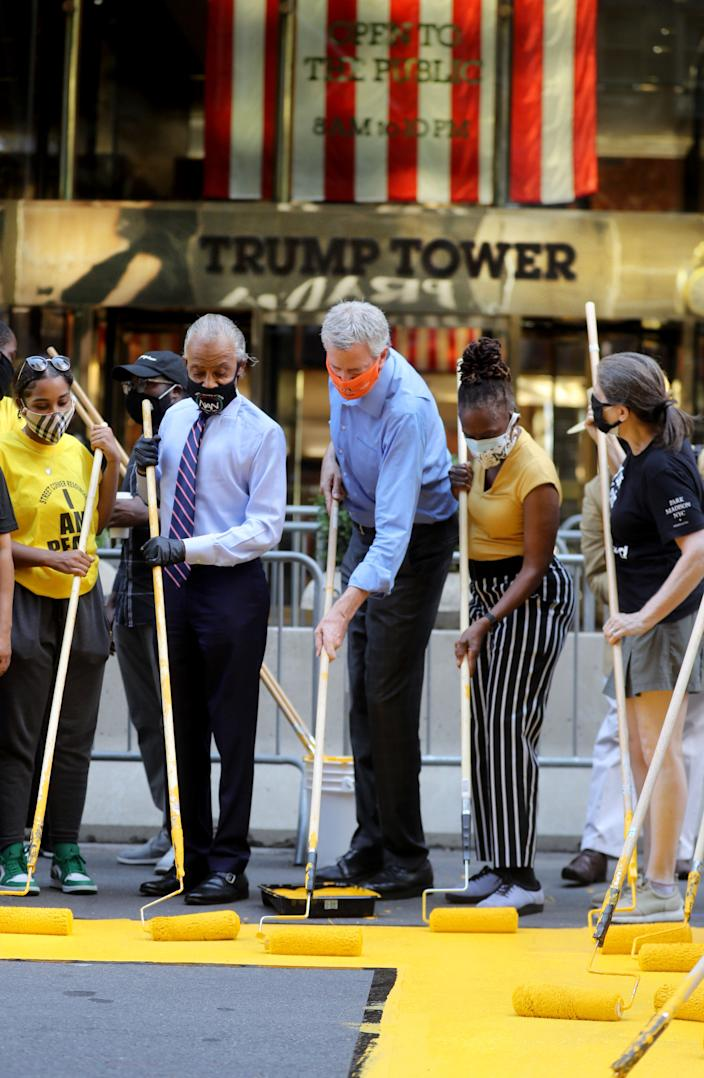 New York City Mayor Bill de Blasio, his wife Chirlane McCray, and the Rev. Al Sharpton assist activists in painting Black Lives Matter on Fifth Ave. in front of Trump Tower