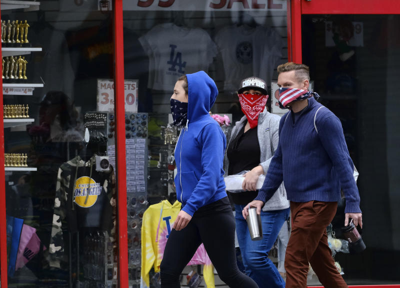 Pedestrians wearing masks during the coronavirus outbreak walk along a deserted Hollywood Boulevard, Sunday, April 5, 2020, in the Hollywood section of Los Angeles. The coronavirus mainly is spread though coughs and sneezes. The new coronavirus causes mild or moderate symptoms for most people, but for some, especially older adults and people with existing health problems, it can cause more severe illness or death. (AP Photo/Richard Vogel)
