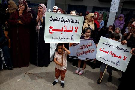 "Palestinian girl holds a placard that reads ""the relief agency is for relief not slaughtering"" during a protest against jobs termination by UNRWA inside its headquarters in Gaza City"