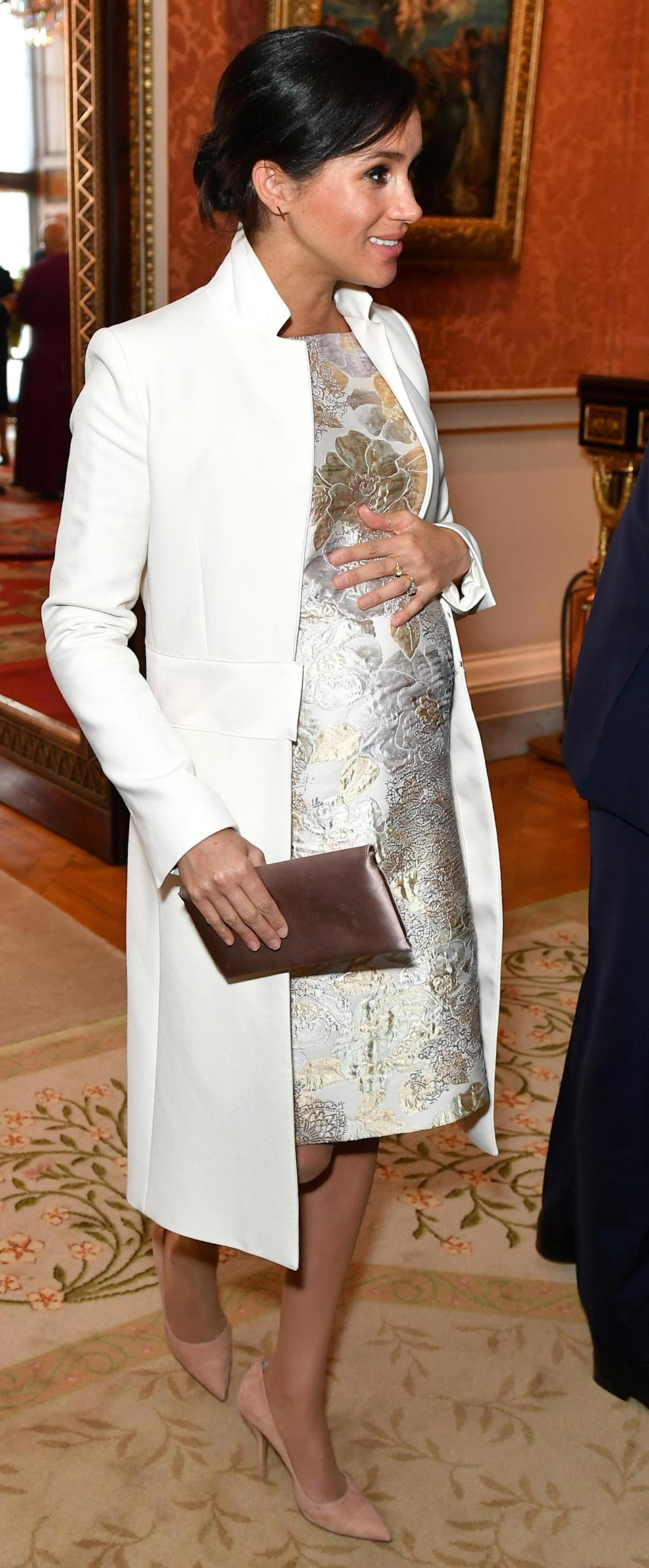 To mark Charles' 50th anniversary as the Prince of Wales, Meghan donned her Amanda Wakeley 'Crombie' coat with a floral brocade dress, her Wilbur and Gussie Oyster Clutch and her Paul Andrews pumps [Photo: Getty]