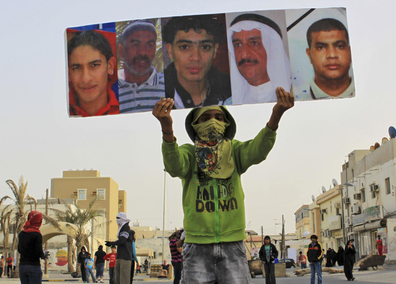 A Bahraini anti-government protester carries pictures of some of the residents of the area who have died during the past year's unrest in the Gulf island kingdom during a demonstration Thursday, March 8, 2012, in Saar, Bahrain, west of the capital of Manama. Clashes erupted with riot police firing tear gas and some protesters throwing Molotov cocktails and stones. (AP Photo/Hasan Jamali)