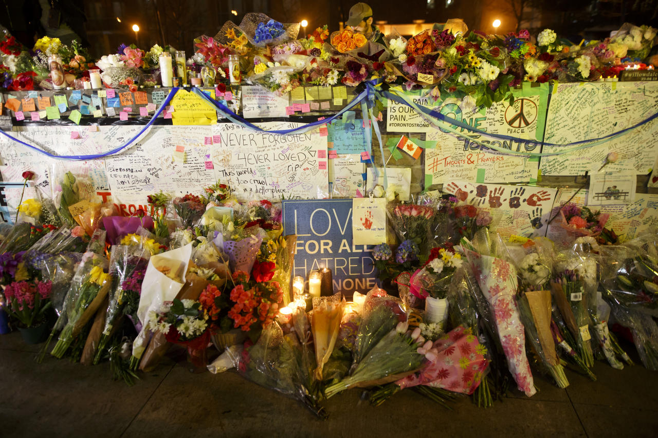<p>Flowers, cards, and words of sympathy adorn a makeshift memorial for victims of the mass killing on April 24, 2018 in Toronto, Canada. (Photo: Cole Burston/Getty Images) </p>